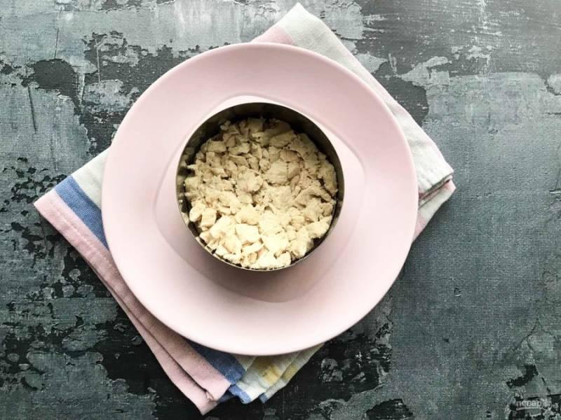 Сервировочное кольцо поставьте на тарелку. Куриное филе нарежьте маленькими кусочками и выложите из него нижний слой салат.