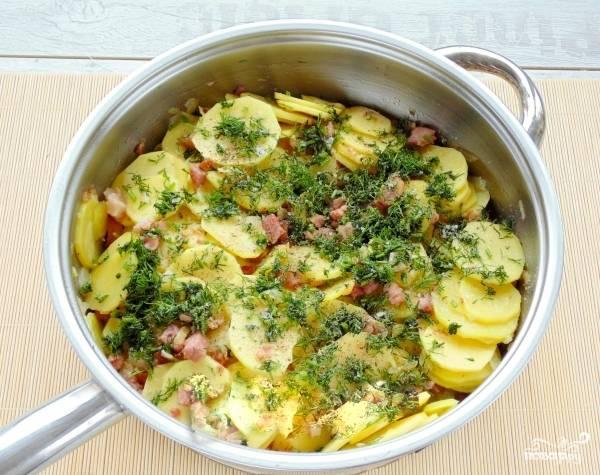 3. Картофель промойте, почистите и нарежьте тонкими ломтиками. Добавьте в сковороду обжариваться. Затем зелень промойте и нашинкуйте, также выложите к остальным ингредиентам в сковороду. Обжаривайте все вместе еще примерно 10-12 минут, затем снимите с огня и поставьте остывать.