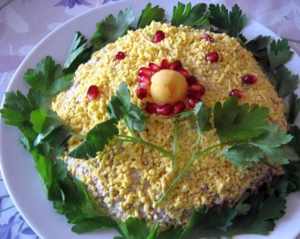 5. Теперь поверх майонеза равномерно распределяем тертые яичные желтки, и украшаем по желанию зеленью и зернами граната. Салат готов!