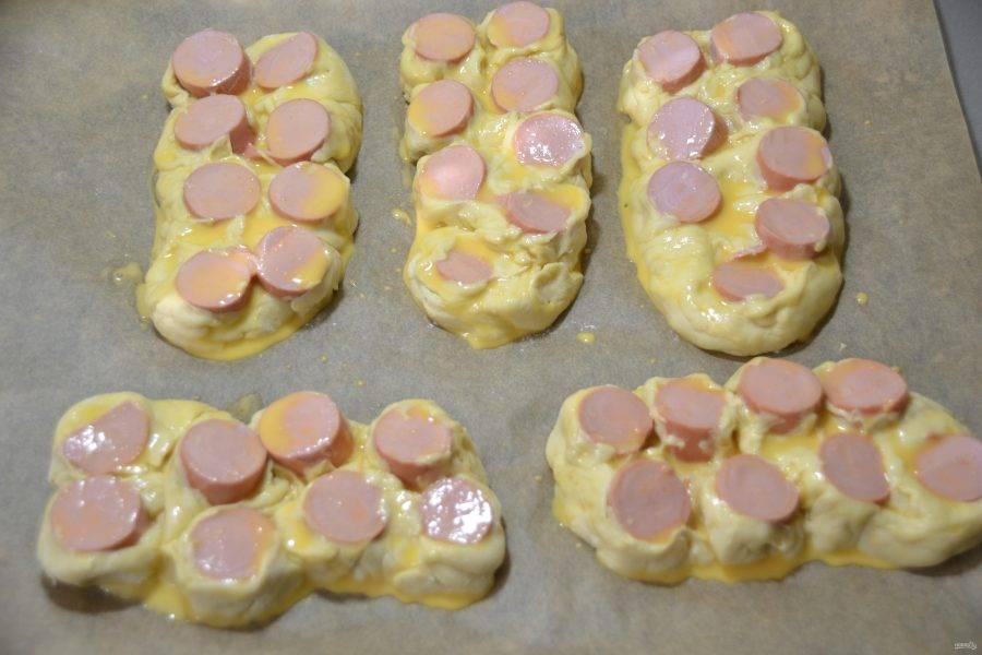 Смажьте булочки желтковой смесью.