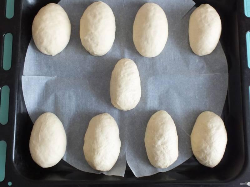 Выложите булочки на выстеленный пергаментом противень. Разогрейте духовку до 180 градусов. Поставьте выпекаться булочки на 20 минут, до золотистого цвета.