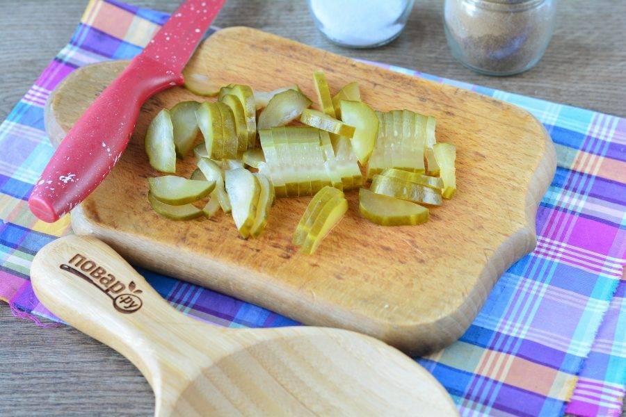 Нарежьте полосками соленые огурцы.