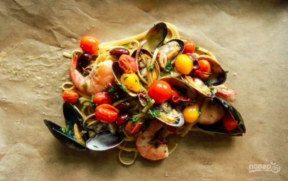 Духовку разогрейте до 200 градусов. Смешайте пасту с морепродуктами, по необходимости добавьте соль и перец. Выложите пасту на 2 больших куска пергамента и каждый заверните.