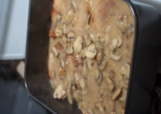 8. Грибы выложить в форму с мясом и отправить ее в заранее разогретую духовку. Готовится свинина, запеченная с грибами в домашних условиях около 1 часа, чтобы мясо было нежным и сочным.