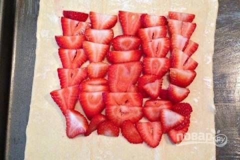 Помытую и обсушенную клубнику нарезаем на небольшие кусочки и выкладываем на тесто. По краям оставляем пустое место.
