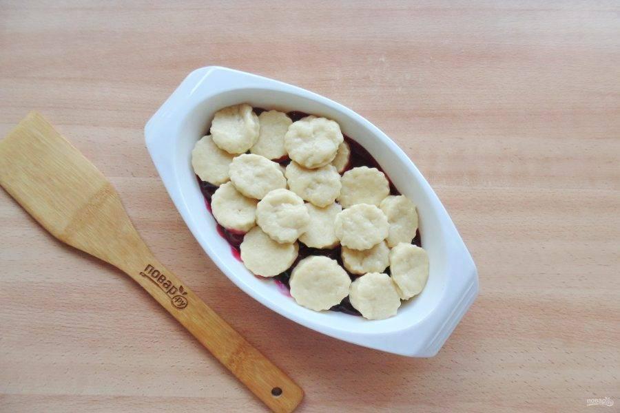 Тесто раскатайте в пласт, и с помощью формы нарежьте кружки. Выложите их на вишню.