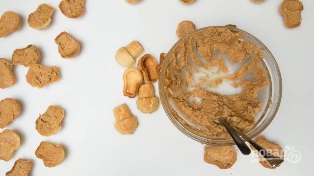 Для наполнения взбейте масло вместе с вареной сгущенкой. Добавьте крошки печенья и перемешайте.