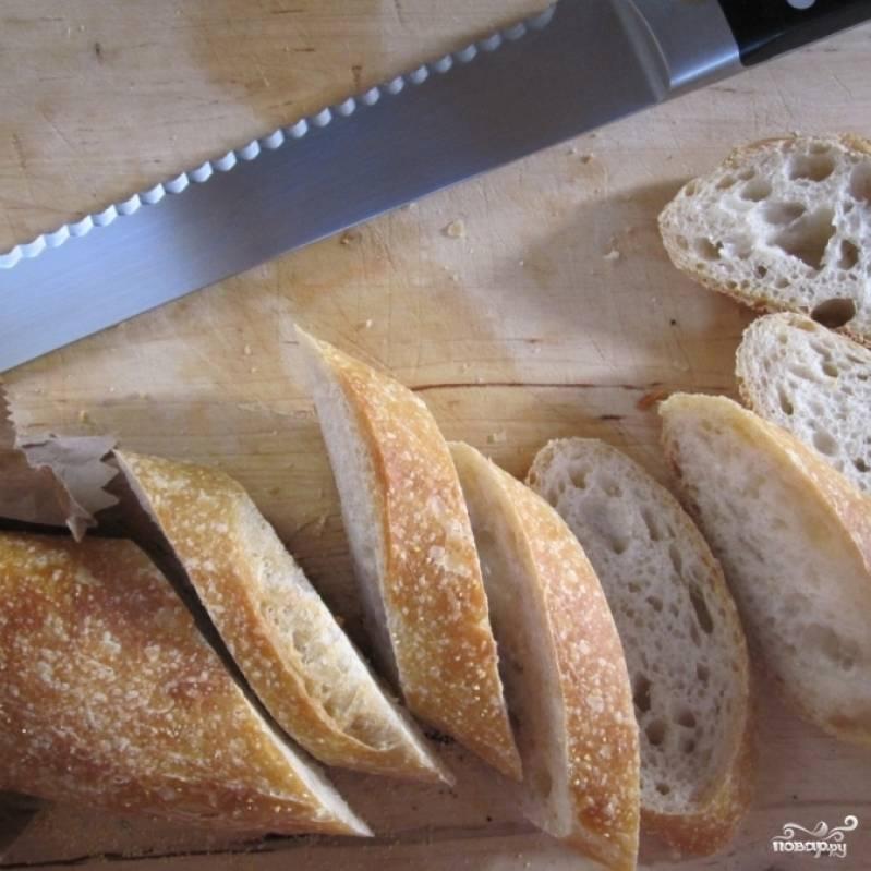 Багет нарезаем на тонкие ломтики. Ломтики багета можно подсушить в духовке или на сухой сковороде, однако мне нравится брускетта с козьим сыром на мягком, не подсушенном багете, поэтому я с ним ничего не делаю - просто нарезаю и все.