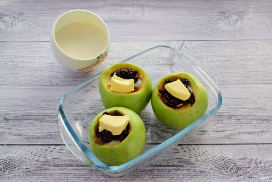 2.     В небольшой посуде соедините сахар, корицу, варенье, измельченные орехи. Выложите яблоки в форму для выпечки и заправьте сердцевины сахарной смесью. Сверху положите по кусочку сливочного масла. Выпекайте в разогретой духовке около 30-40 минут.