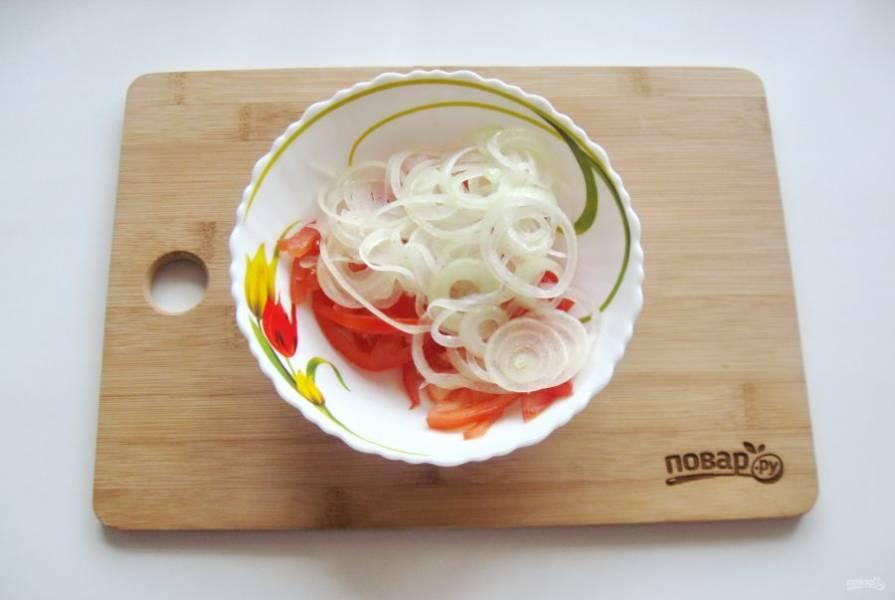 Выложите нарезанный лук и помидоры в салатник.