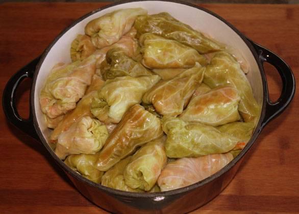 8. Осталось только потушить голубцы. Их можно готовить в духовке или на плите. Итак, выложите голубцы в большую толстостенную кастрюлю. Приготовьте подливу. Для этого обжарьте оставшиеся 2 морковки (натрите их на терке) на масле с вегетой до мягкости, добавьте сметану и около стакана томатного пюре, перемешайте. Вылейте подливу в кастрюлю, добавьте воду от вареной капусты. На плите доведите до медленного кипения и тушите под приоткрытой крышкой в течение 40 минут. В духовке запекайте при температуре 200 градусов в течение 20-25 минут, затем понизьте до 175 и запекайте еще час.
