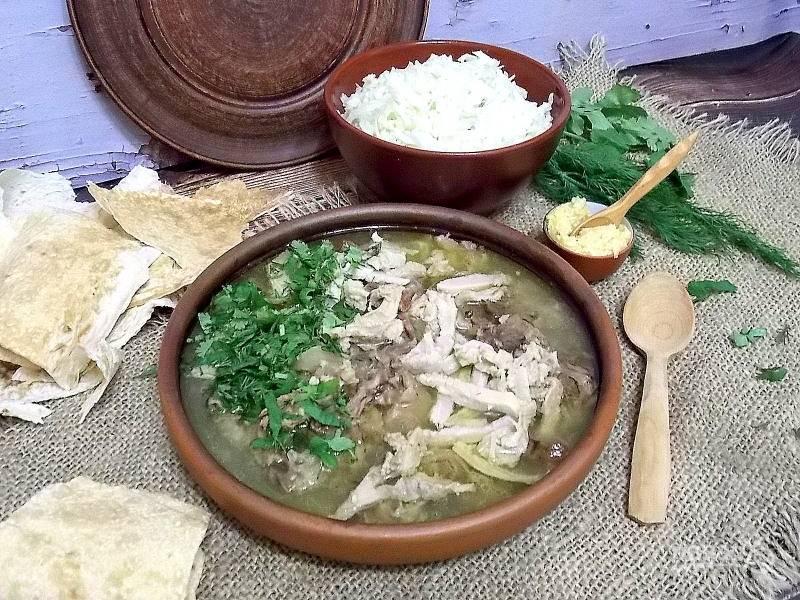 Положите в тарелку чеснок, налейте горячий хаш, посыпьте рубленной зеленью и подавайте с салатом из редьки и тонким лавашем.