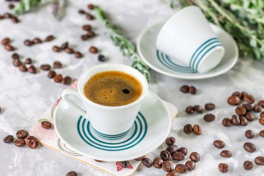 Сварите кофе в кофемашине или в турке на плите. Он обязательно должен быть крепким, ароматным и бодрящим. Ошпарьте кипятком лимон и натрите лимонную цедру. Выложите небольшое ее количество в чашки и влейте кофе.