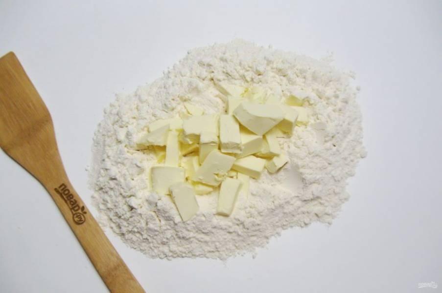 Муку насыпьте в миску или на стол. В середину выложите холодное сливочное масло.