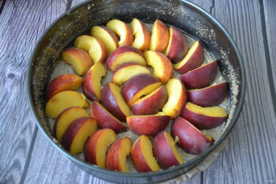 Помойте персики, разрежьте на дольки, плотно выложите на дно формы.