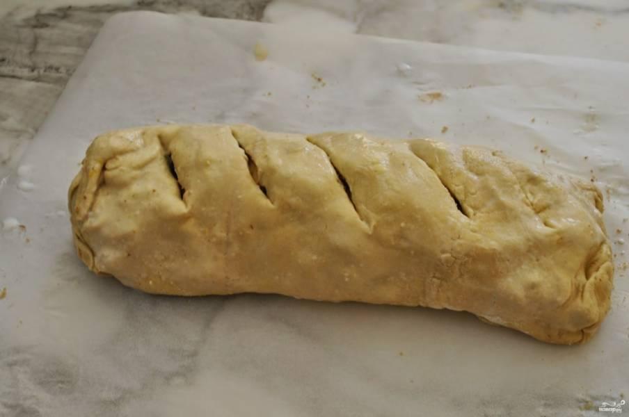 С помощью пергамента (или без него) заверните тесто с начинкой в рулет, закрепите шов с помощью пары капель молока. Не забудьте перевернуть изделие швом вниз. Сделайте несколько надрезов на поверхности штруделя.
