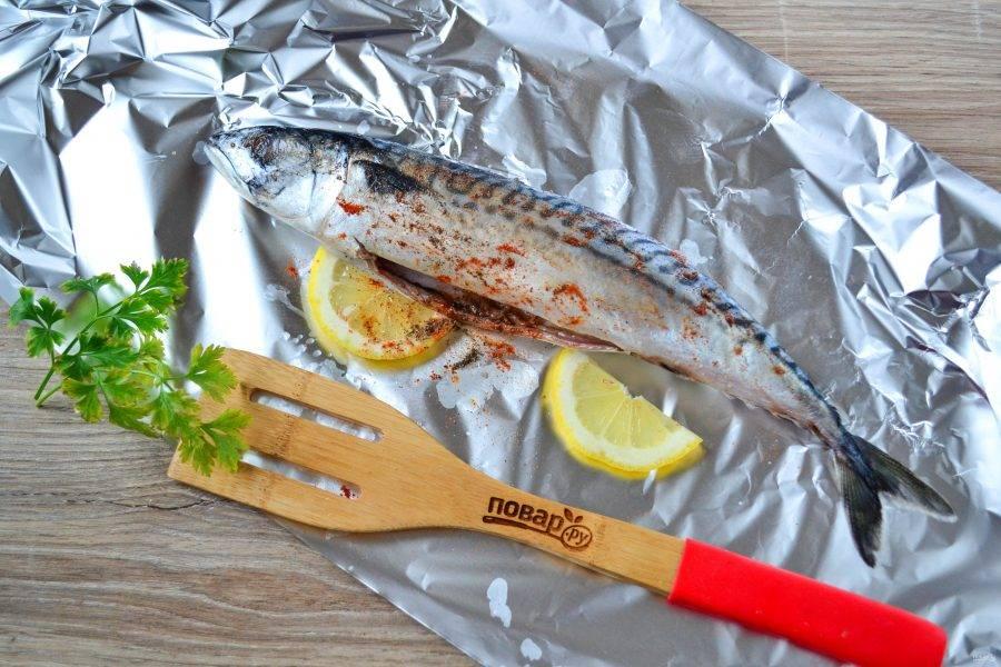 Подготовленную рыбку натрите солью, перцем и паприкой, сбрызните лимонным соком. Выложите рыбу на фольгу и положите к ней пару ломтиков лимона.
