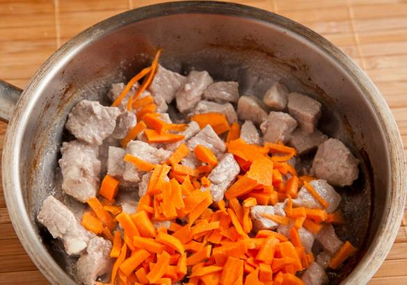 Морковь нарежьте тонкой соломкой и добавьте к мясу. Жарьте еще несколько минут.