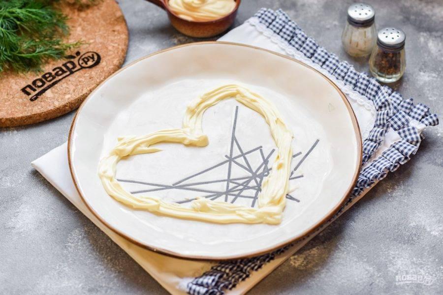 Подготовьте тарелку, в которой будем собирать салат. При помощи майонеза нарисуйте на тарелке сердце. Размер вы можете выбирать под количество своих гостей.