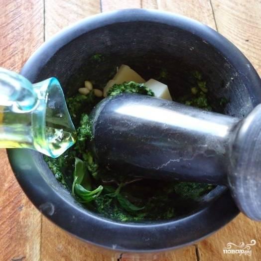 Затем добавляем в ступку остальные ингредиенты - сыр, орехи, чеснок и оливковое масло. Толчем до однородности.