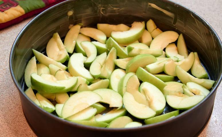 3. Жаропрочную форму смажьте немного сливочным маслом и выложите яблочки.