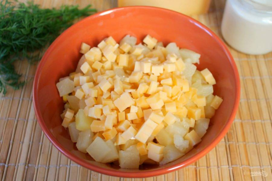 Твердый сыр режем маленькими кубиками и высыпаем в салат.