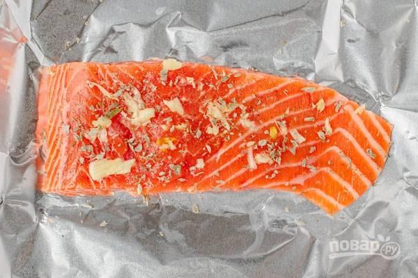 1.Вымойте рыбу и вытрите ее насухо, щедро полейте оливковым маслом. Выложите на фольгу стороной с оливковым маслом. Очистите чеснок и измельчите его, посыпьте половину чесночной смеси над рыбой, добавьте соль, перец, тимьян.