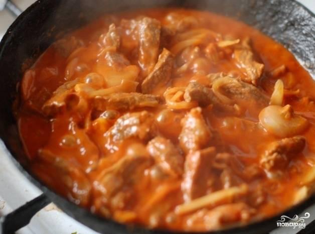 Дальше отправляем лук с соусом к говядине и перемешиваем. Накрываем крышкой и тушим около часа, периодически помешивая и доливая горячей воды.