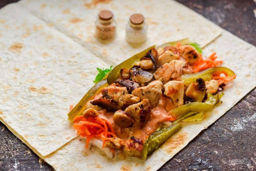 Выложите поверх соуса индейку и грибы, добавьте нарезанные огурцы.