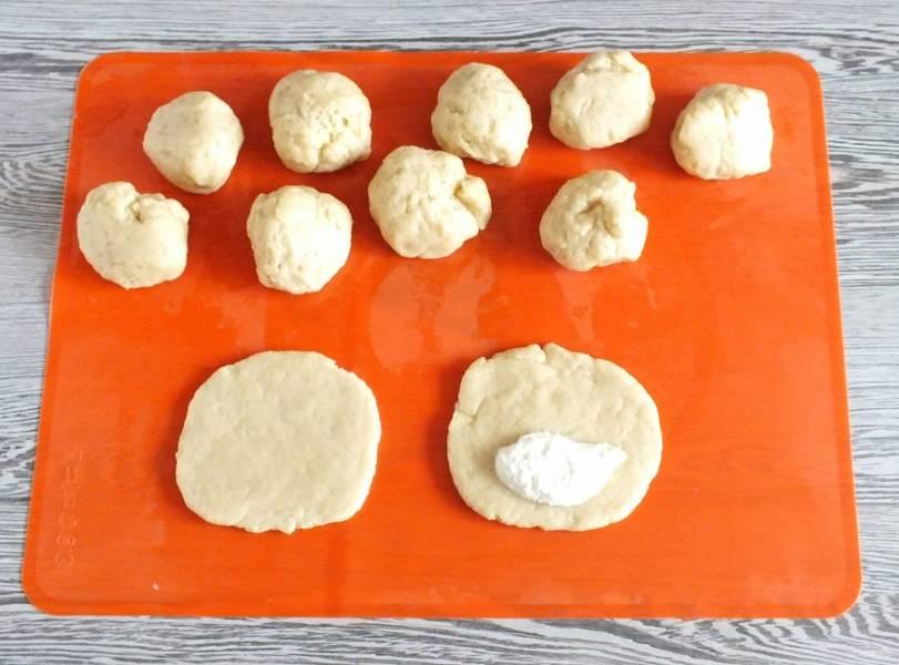 Каждую часть раскатайте в пласт толщиной 0,5 см. Выложите на край лепешки столовую ложку начинки.