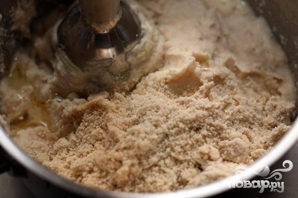 4.В кофемолке или блендере в порошок перемалываем кунжут и добавляем в смесь из фасоли. Сюда же добавляем оливковое масло и продолжаем измельчать. У нас получается консистенция паштета, пластичная и густая.