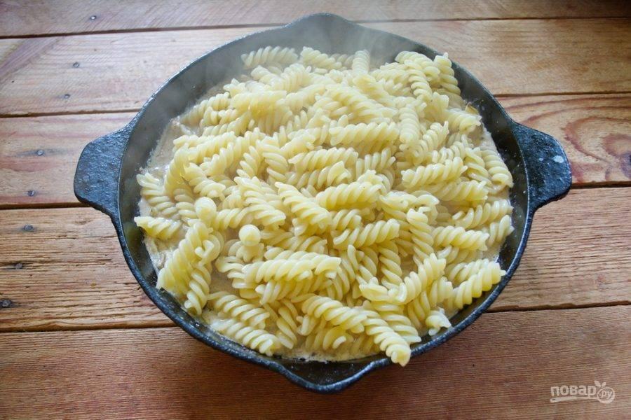 Отваренные макароны откиньте на сито и немного воды сохраните. Макароны добавьте в сковороду к соусу. При необходимости влейте немного воды, в которой варились макароны.