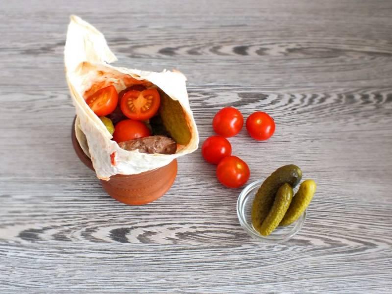 Далее выложите 2-3 котлетки, корнишоны и помидорки черри.