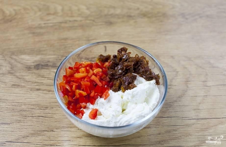 Вяленые помидоры и сладкий перец нарезаем на мелкие квадратики, перекладываем в глубокую миску. Добавляем к ним мягкий сыр, солим, посыпаем перцем и тщательно все перемешиваем.