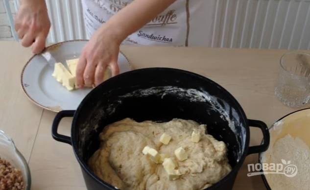 10.Сливочное масло заранее достаньте из холодильника, затем нарежьте его небольшими кубиками и добавьте в тесто, вмешайте его, оставьте тесто на 30-40 минут.