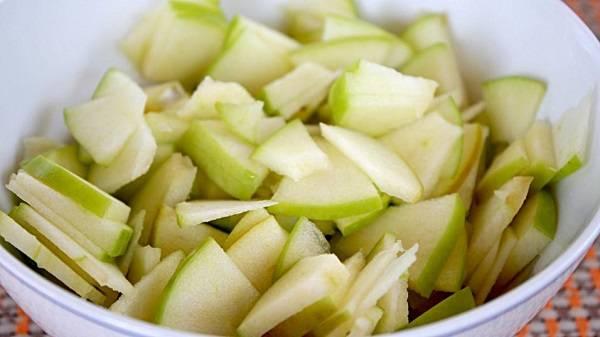 2. Вымыть и обсушить яблоко. В рецепт приготовления простого салата из свежей капусты лучше всего использовать плотные зеленые яблоки с кислинкой. Выжать сок лимона и полить им яблоки (это позволит сохранить им свой цвет и не потемнеть).