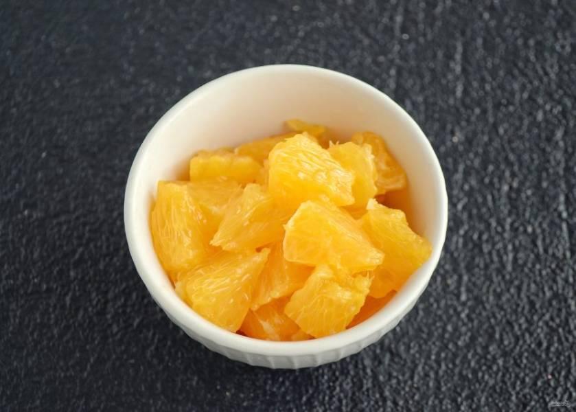 Апельсин нарежьте на маленькие кусочки.