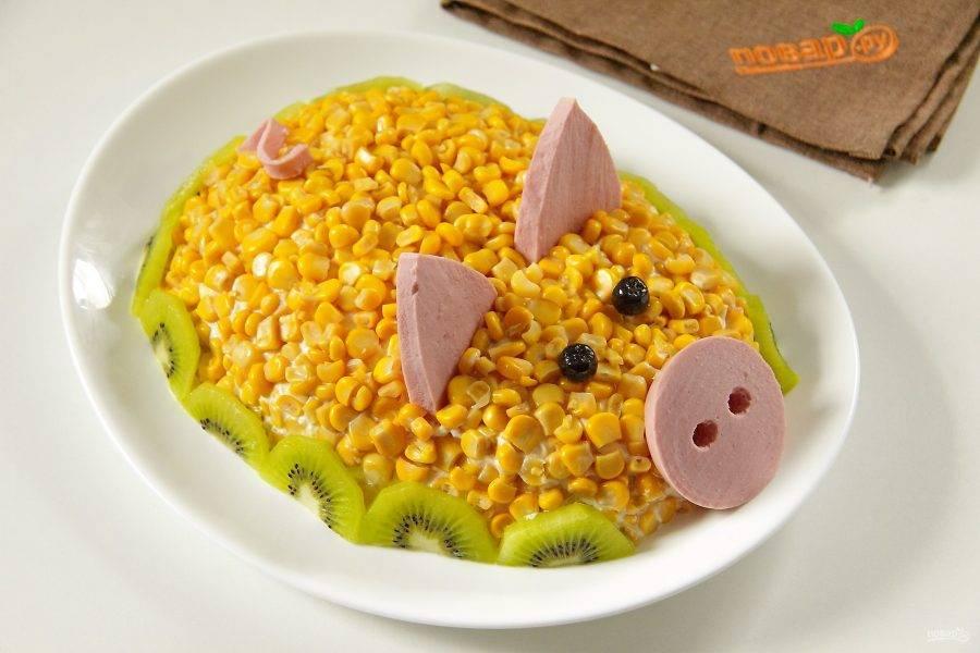 """Из маслин или подходящих по размеру ягод делаем глаза, из кусочков колбасы ушки, пятачок и хвостик. Киви нарезаем кружочками, кружочки режем пополам и украшаем салат по низу. Салат """"Новогодняя свинка"""" готов. Приятного аппетита!"""