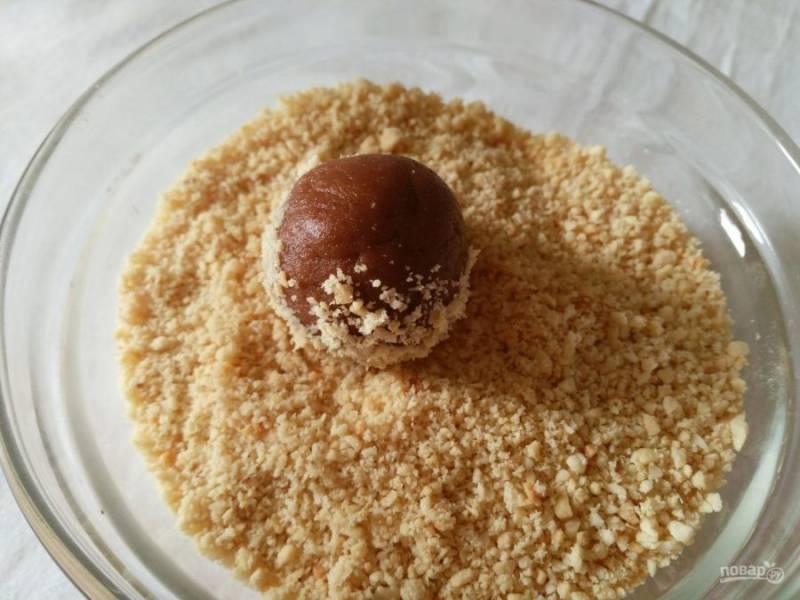 Как только смесь перестанет быть горячей, сформируйте из неё небольшие шарики, а затем обмакните их в измельчённые орехи и кокосовую стружку.