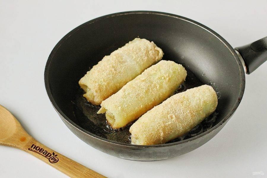 Окуните каждый голубец во взбитые с солью яйца (можно добавить по желанию молотый перец) и обваляйте в сухарях. Выкладывайте голубцы с сосисками на разогретую сковороду с растительным маслом.