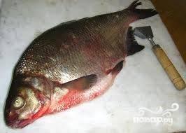 2. Во время того, как готовится гречневая каша, нужно приступать к рыбке. Промываю леща под проточной водой, очищаю от чешуи и опять промываю, чтобы убрать все остатки от чешуи. Затем делаю надрез от головы рыбы до хвоста и удаляю все внутренности. Опять промываю под водой и слегка высушиваю кухонным бумажным полотенцем. Рыбку солю и перчу как внутри, так и снаружи.