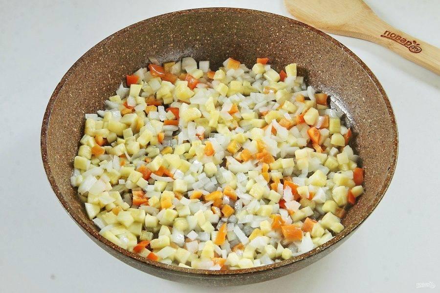 Лук, кабачок и болгарский перец нарежьте небольшими кубиками. Обжарьте на растительном масле до мягкости.