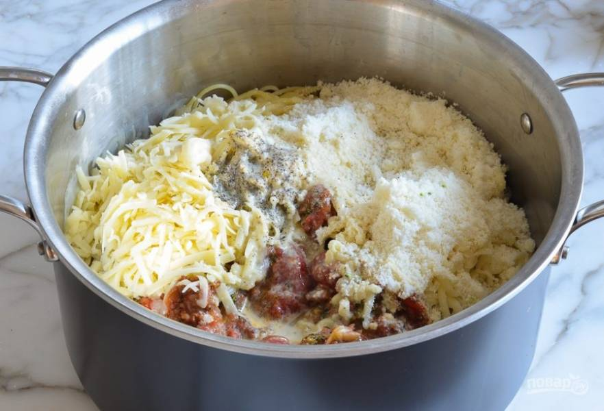 8. Затем спагетти перемешайте с продуктами со сковороды и заливкой. Ещё мелко натрите весь сыр, оставив только 1/3 пармезана на потом.