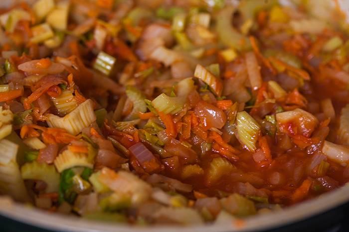 Теперь мы очищаем помидор от кожицы и перетираем его в пасту, выкладываем на сковороду, или же просто добавляем столовую ложку уже готовой томатной пасты. Вливаем пару ложек воды, перемешиваем все, накрываем сковороду крышкой, тушим овощи несколько минут.