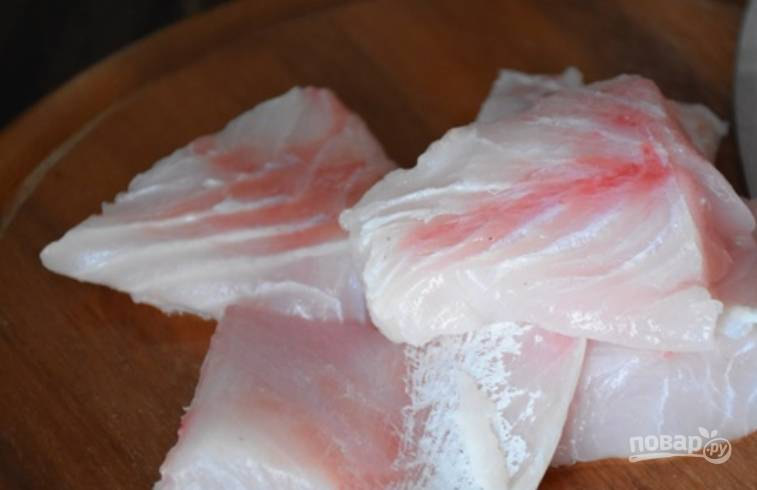 Филе окуня промойте, обсушите и порежьте порционными кусочками. Присыпьте перцем и солью.