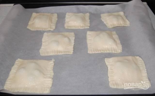 5.Положите пирожки на противень, покрытый бумагой для выпечки, и закрепите края зубчиками вилки. Смажьте поверхность пирожков смесью воды с сахаром.
