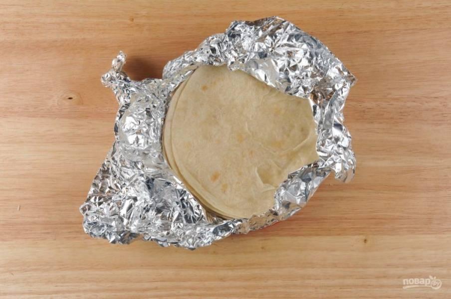 Тортильи заверните в фольгу. Уберите их на 6 минут в духовку при 180 градусах.