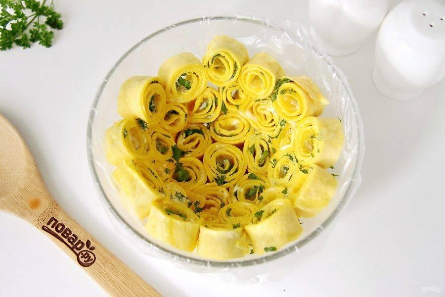 Глубокий круглый салатник застелите пищевой пленкой и равномерно разложите по всей поверхности рулетики из блинчиков.