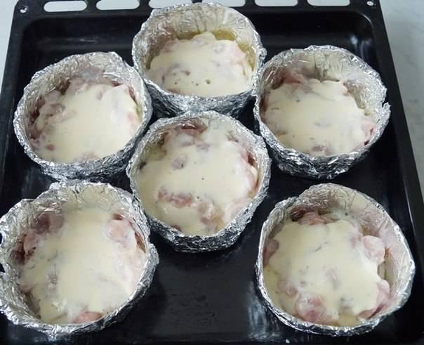 5. В отдельной мисочке взбить яйца со сметаной и щепоткой соли. Добавить немного яичной смеси в каждую форму так, чтобы она покрыла начинку.