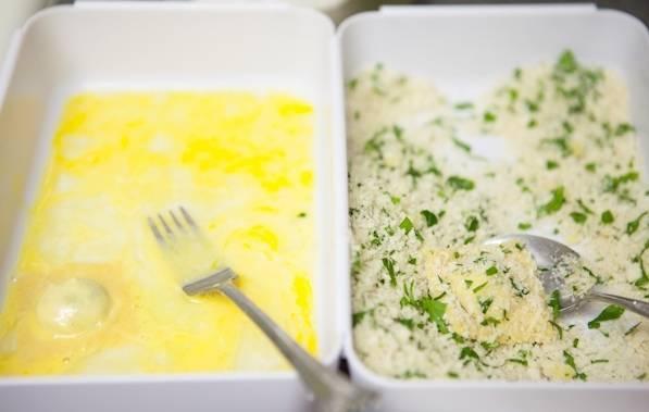 Обмакните равиоли сначала в яйцо, а затем в тертый сыр с зеленью.